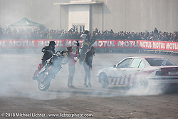 Drift cars skidding circles around stunting motorcycles wheelie-ing around each other during Motor Bike Expo. Verona, Italy. January 24, 2016.  Photography ©2016 Michael Lichter.
