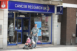 © London News Pictures. 14/07/2013. COPY AVAILABLE BELOW…. One of two Cancer Research UK shops on Orpington High Street, Kent. Orpington High street now has 12 charity shops  in one short stretch, with Cancer Research UK having two shops on different sides of the high street almost facing each other.  COPY AVAILABLE HERE:  http://tinyurl.com/nhtxtyd<br /> <br /> Photo credit :Grant Falvey/LNP