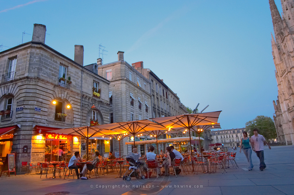 A cafe on the place pey berland in Bordeaux, outside seating terrasse lit by electric lights, people sitting drinking and walking on the square, Place Pey Berland. city Bordeaux Gironde Aquitaine France