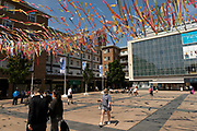 People underneath colourful bunting hanging in Broadgate near the Godiva statue in the UK City of Culture 2021 on 23rd June 2021 in Coventry, United Kingdom. The striking statue of Lady Godiva stands in the citys central square, Broadgate. Sculpted by William Reid-Dick, it was unveiled in 1949 and is one of the few statues of horses outside the capital to be listed Grade II. The UK City of Culture is a designation given to a city in the United Kingdom for a period of one year. The aim of the initiative, which is administered by the Department for Digital, Culture, Media and Sport. Coventry is a city which is under a large scale and current regeneration.