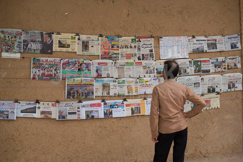 Iran, Yazd, 01.09.2016: Ein Mann liest ausgehängte Tageszeitungen vor einem Zeitungskiosk in Yazd, Provinz Yazd, Zentral-Iran.