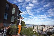 Toeristen maken foto's van San Francisco bij Lombard Street. De Amerikaanse stad San Francisco aan de westkust is een van de grootste steden in Amerika en kenmerkt zich door de steile heuvels in de stad.<br /> <br /> Tourists make photos in and of San Francisco. The US city of San Francisco on the west coast is one of the largest cities in America and is characterized by the steep hills in the city.