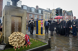 The Royal British Legion standard is lowered at the war memorial during a service of remembrance at Royal Wootton Bassett, Wiltshire.