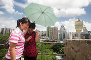 Tourists talking on the phone with Macau's cityline on the background.