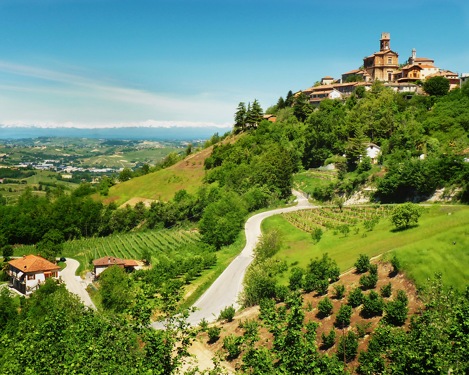 The Piedmont region of Italy, Piemonte, blanketed in hills, each with its own village, castle, and vineyards.  Connecting all of these interesting places is a web of roads twisting up and down the slopes from village to village.  In the background of this image are the snow covered Alps.