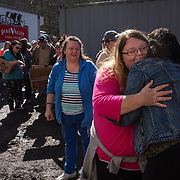 Floria White gets a hug from Priscella Cline Smith as she waits in line at Paradise Island in Logan County, W.Va., on Thursday, February 21, 2019.