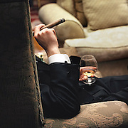 low key photo of man whose face is concealed holding a cigar and a snifter of cognac during a wedding reception jazz after-party