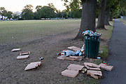 After a late-night party by park-users during the Coronavirus pandemic, litter and waste is strewn across the grass in Ruskin Park, on 30th July 2020, in Lambeth, south London, England.