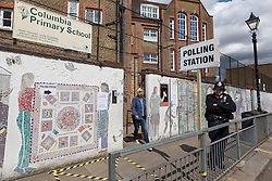© Licensed to London News Pictures. 07/05/2015. London, UK. A voter leaving their local polling station as a police officer stands outside in Columbia Road, Tower Hamlets, east London today. Photo credit : Vickie Flores/LNP