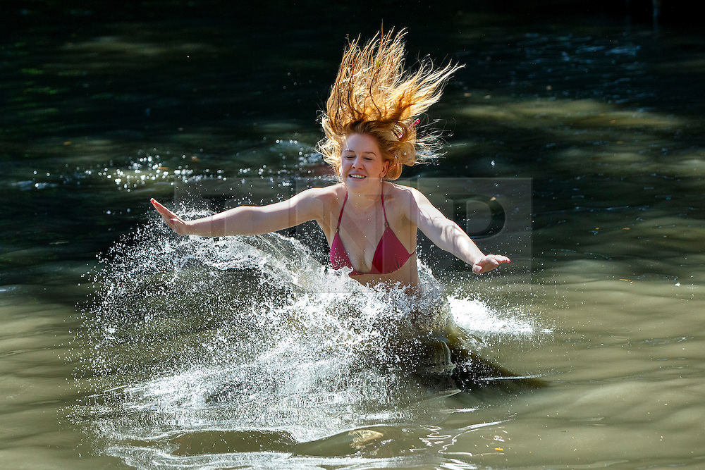 © Licensed to London News Pictures. 12/08/2016. London, UK. Ayla Smith jumps into Hampstead Heath Mixed Bathing Pond in north London as people enjoy hot weather on Friday, 12 August 2016. Photo credit: Tolga Akmen/LNP