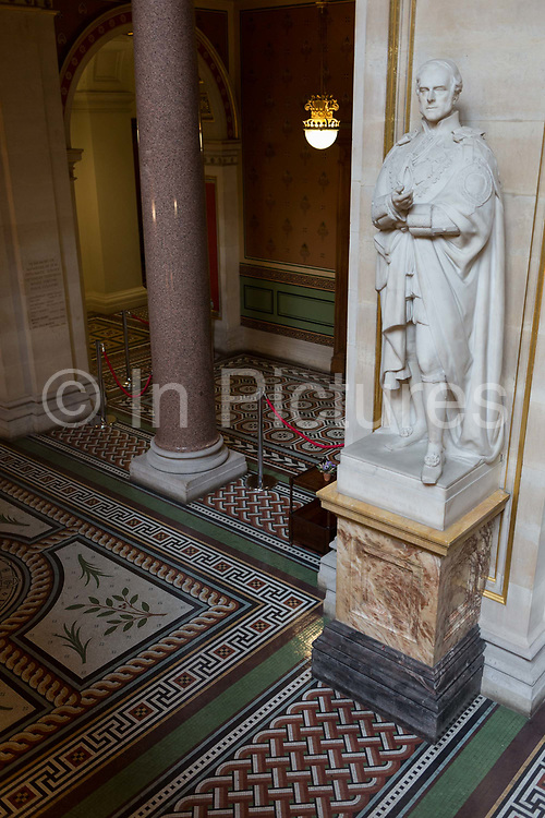 The statue of the 4th Earl of Clarendon KG GCB at the foot of the Grand Staircase in the Foreign and Commonwealth Office FCO, on 17th September 2017, in Whitehall, London, England. George William Frederick Villiers, 4th Earl of Clarendon KG GCB PC 1800–1870, was an English diplomat and statesman. The main Foreign Office building is in King Charles Street, and was built by George Gilbert Scott in partnership with Matthew Digby Wyatt and completed in 1868 as part of the new block of government offices which included the India Office and later 1875 the Colonial and Home Offices. George Gilbert Scott was responsible for the overall classical design of these offices but he had an amicable partnership with Wyatt, the India Office's Surveyor, who designed and built the interior of the India Office.