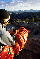 A backpacker takes in the sunrise while camping in the Wind River Mountains, Wyoming.