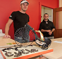 """Miles Chase and CJ Best of MC Cycle admire their """"high wheeled"""" shoe created by Sue and Randy Bullerwell of All My Life Jewelers during the Downtown Still Has Sole event ongoing through Thursday.  (Karen Bobotas/for the Laconia Daily Sun)"""