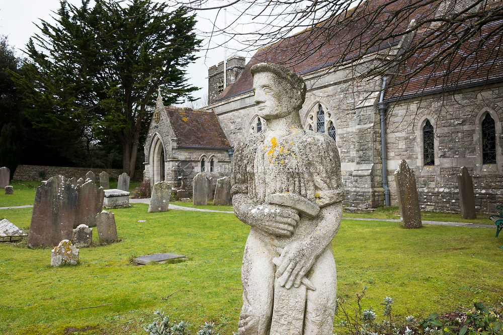Stone lichen covered statue in a graveyard near a stone church in Swanage, England.