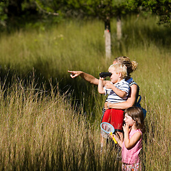 A woman and her young children watch for birds in a grassy field near the Eightmile River in Lyme, Connecticut.  The Nature Conservancy's Pleasant Valley Preserve.
