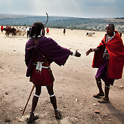 Sherssen,to the right, is greeting a friend. Its the end oof the day and the cattle and goat market day in Ilkerin is almost over. It is mainly Maasais who live in the Loita Hills up above the Serengeti plains. They live in small villages and communities called bomas and live mainly of raising and selling live stock such as cattle and goats. Its a very remote region in Kenya, hard to get to without a four wheel drive with very little infrastructure and up till 2010 no mobile phone network. The Maasais are well known though out Kenya and the world for their colorful clothing and their way of keeping their old traditions alive...Sherssen is local and is a member of the S.A.F.E theatre group. S.A.F.E is a charity which educates children and young people about life skills and how to protect themselves from HIV and other STIs through performance. They also do performances about Female Genital Mutilation, an old tradition amongst the Maasais in Loita and a very brutal and controversial custom which S.A.F.E is trying to eradicate.