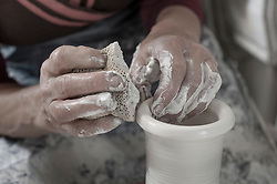 Close-up of female potter moulding clay using cleaning sponge in workshop, Bavaria, Germany