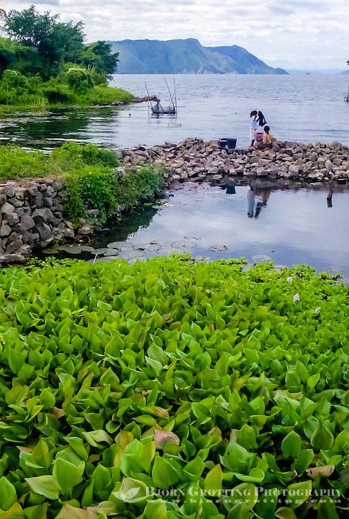 Indonesia, Sumatra. Samosir. Toba landscape from TukTuk, Girls doing the laundry. South Tuk Tuk looking east.