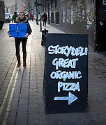 Women walking past sign in Brick Lane