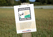 Operation Bumble Bee sign on by field, Suffolk, England a scheme to promote insect habitat in arable farming areas, Hollesley, Suffolk, England