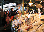 Traditional fish throwing at Pike Street Public Market Center and Farmers Market, in downtown Seattle, Washington, USA.