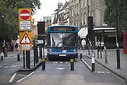 Bus approaching rising bollard street barriers, Cambridge, England