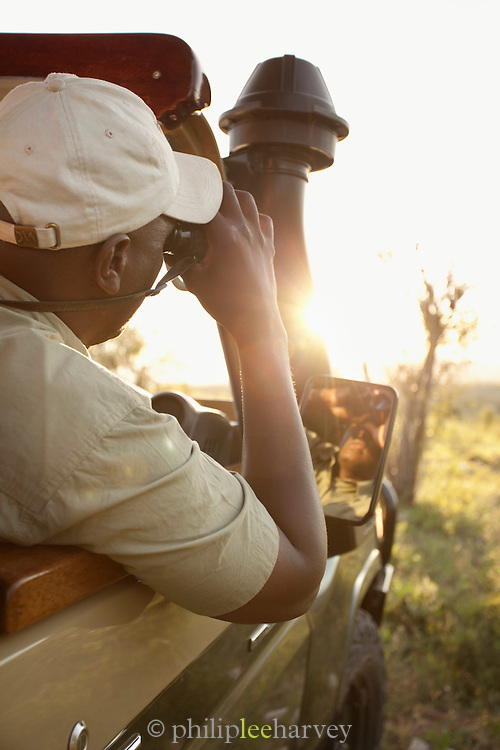 A guide and spotter looks for wildlife in the Maasai Mara National Reserve in Kenya