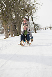 Man pushing woman on sledge in snow, Bavaria, Germany