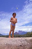Niño indígena con mariposas amarillas sobre piedra en el río Autana, Amazonas, Venezuela.