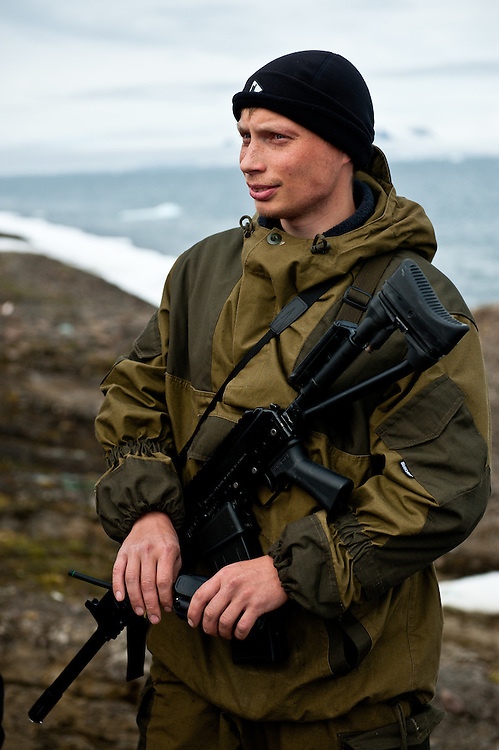 A ranger in the Russian Arctic National Park, on the shore of one of the islands of Franz Josef Land with the rifle he carries to ward off polar bears.