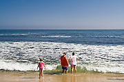 Two woman and a child stand in the water looking out to the ocean at Laguna Beach, California.
