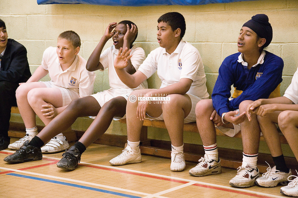 Group of secondary school students watching others playing indoor cricket in the school sports hall,