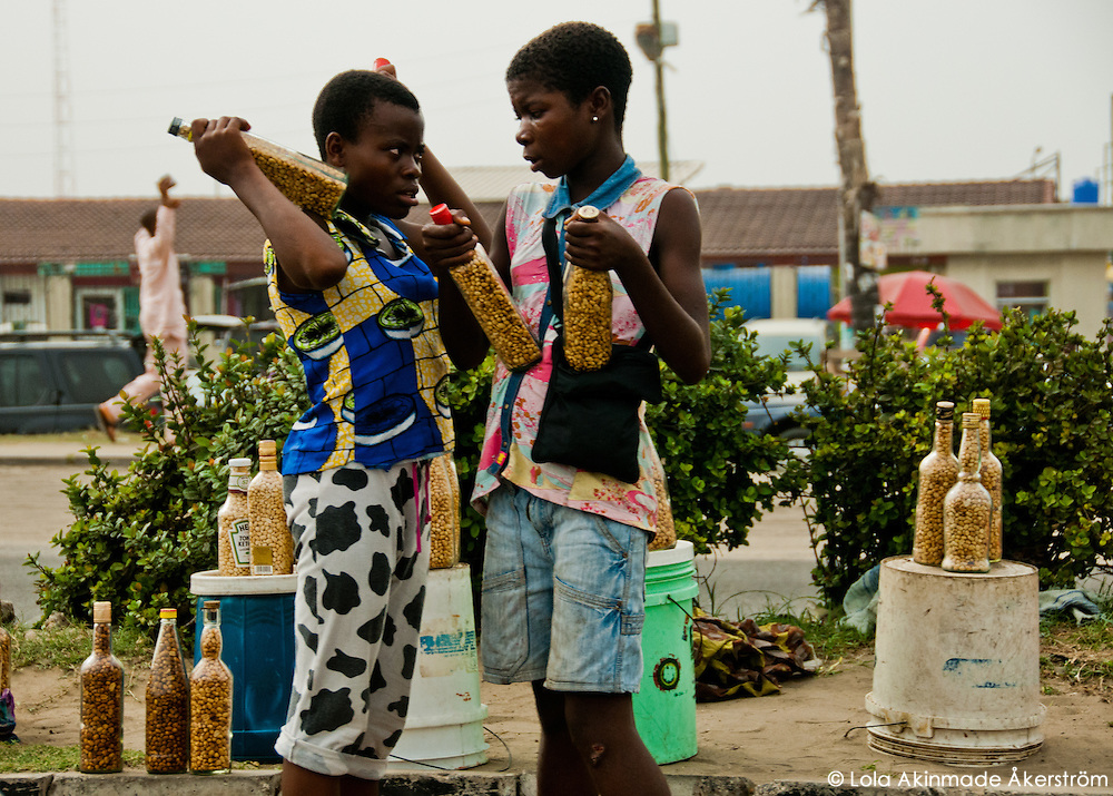 Nigeria - Female street hawkers selling groundnuts (peanuts)