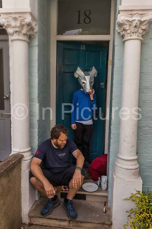 Father sitting on the steps and son in a cow mask, relaxing in their front garden during the coronavirus pandemic on the 10th May 2020 in London, United Kingdom. Although young people may not have a lot of physical space, it is important that they can find ways of creating some mental space.