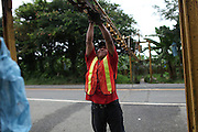 Mateo Santos, Ngäbe member of COOBANA, guards a banana cluster rail that crosses the Changuinola to Sixaola highway. COOBANA, Finca 51, Changuinola, Bocas del Toro, Panamá. September 3, 2012.