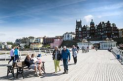 Holidaymakers enjoying the sunshine on Cromer Pier in Norfolk.