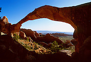 A Hiker stands below Landscape arch in Arches National Park, at 89 meters across it's the world's largest natural arch.