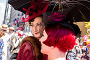 New York, NY - April 16, 2017. Two women under an umbrella, wearing a headpiece that harkens to the 1930s at New York's annual Easter Bonnet Parade and Festival on Fifth Avenue.