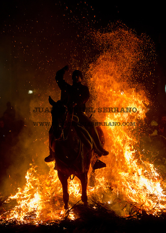 A man rides a horse through a bonfire in San Bartolome de Pinares, Spain, Monday, Jan. 16, 2012, in honor of Saint Anthony, the patron saint of animals. On the eve of Saint Anthony's Day, hundreds ride their horses trough the narrow cobblestone streets of the small village of San Bartolome during the 'Luminarias' a tradition that dates back 500 years and is meant to purify the animals with the smoke of the bonfires and protect them for the year to come. Photo by Juan Manuel Serrano Arce