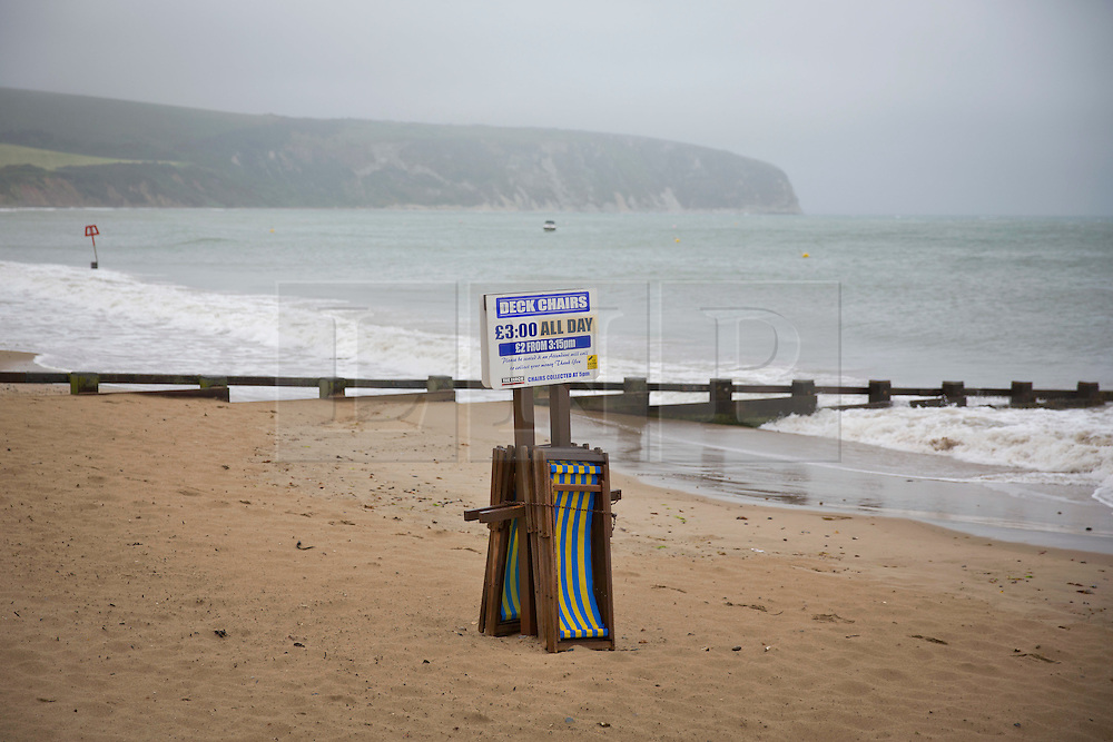 © London News Pictures. 02/06/2015. United Kingdom, Swanage. Deck chairs piled up on the beach. Grey skies cover the sky over a windy seafront at Swanage, Dorset, on June 2, 2015. Photo credit: LNP