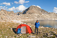 Noel Lake backcountry camp with adult male backpacker in blue jacket enjoying the view. Bridger Wilderness. Wind River Range, Wyoming