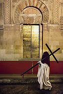 A nazareno carrying a cross passes by the islamic architecture of one of the doors along the wall surrounding the Mezquita in Cordoba. Andalusia, Spain.