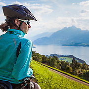 A woman taking a break while moutain biking in the area of Seebodenalp - Weggis on Mount Rigi in Switzerland.
