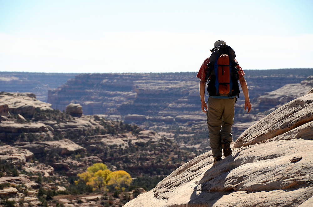 Backpacker on sandstone slope in Southern Utah.