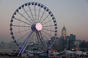 A giant Ferris wheel on the harbour front with a 'Happy New Year 2015'. 7 million people live on 1,104km square, making it Hong Kong the most vertical city in the world.