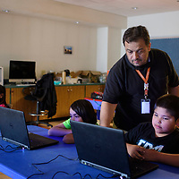 Technology trainer at the public library Markos Chavez helping Harlan Henio, 9, during one of his YouTube classes, Wednesday July 11 at the children's branch of the Octavia Fellin Public Library.
