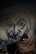 A man warped in a wool blanket, temperature are often below zero celsius during the night. A group of more than 100 migrants are squatting an abandoned building  in the town of Bihac, Bosnia Herzegovina not far from the Croatian border, living without running water electricity and warming themself close to smokey bonfires. January 26, 2021. Federico Scoppa