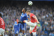 Didier Drogba of Chelsea and Luke Shaw of Manchester United jump for the ball. Barclays Premier league match, Chelsea v Manchester Utd at Stamford Bridge Stadium in London on Saturday 18th April 2015.<br /> pic by John Patrick Fletcher, Andrew Orchard sports photography.
