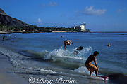 skimboarders at Waikiki Beach with<br /> Diamond Head in the background<br /> Oahu, Hawaii, USA ( Pacific Ocean )