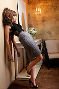 Woman in evening dress leans on wall